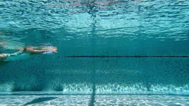 woman doing backstroke kick by using a kickboard in swimming pool - buoy stock videos & royalty-free footage