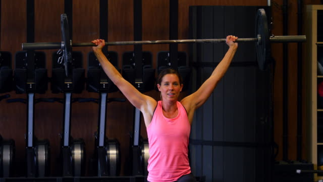 ms woman doing barbell walking lunges while working out in gym gym - cross training stock videos & royalty-free footage