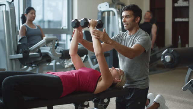 vidéos et rushes de ms woman doing butterflies with weights and trainer in gym / bellevue, washington, usa - salle de gym