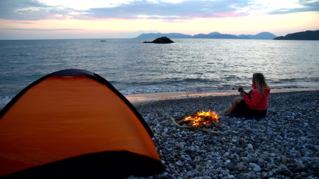 Woman doing camping on the beach in the evening.