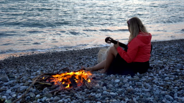 woman doing camping on the beach in the evening. - musician stock videos & royalty-free footage