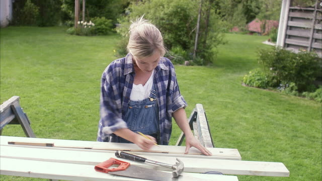 a woman doing carpentry in a garden sweden. - one mid adult woman only stock videos & royalty-free footage