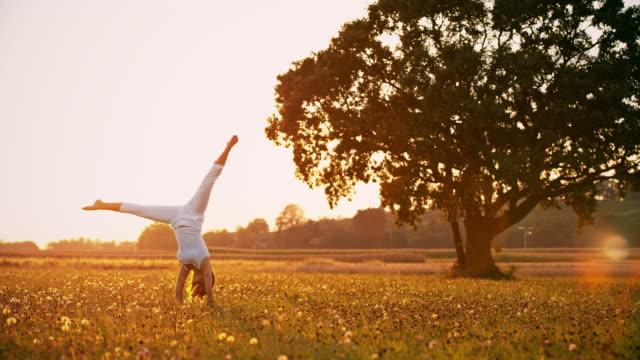slo mo woman doing cartwheel on meadow - cartwheel stock videos & royalty-free footage