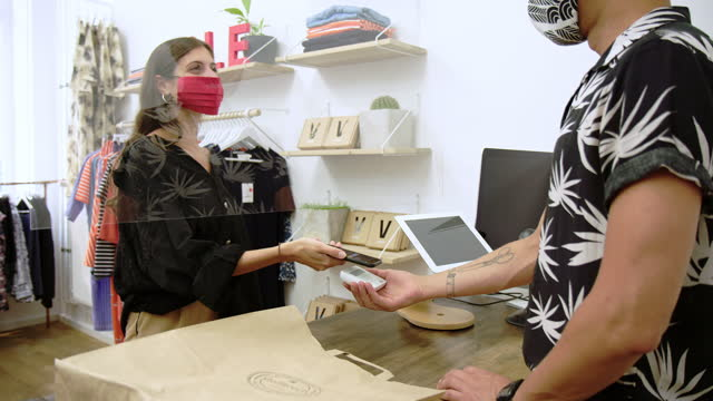 vídeos de stock e filmes b-roll de woman doing contactless payment in clothing store - boutique