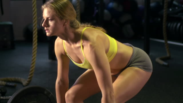 A woman doing deadlifts at the gym. - Slow Motion