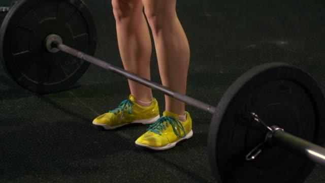 vídeos de stock, filmes e b-roll de a woman doing deadlifts at the gym. - slow motion - peso livre equipamento para exercícios