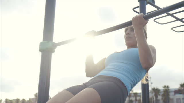 woman doing dips in the park - chin ups stock videos and b-roll footage