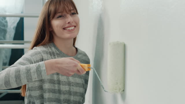woman doing diy project in apartment - paint roller stock videos & royalty-free footage