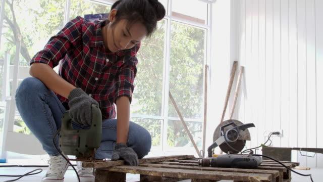 vidéos et rushes de femme des travaux de bricolage, montage de meubles à la maison - reconstruction