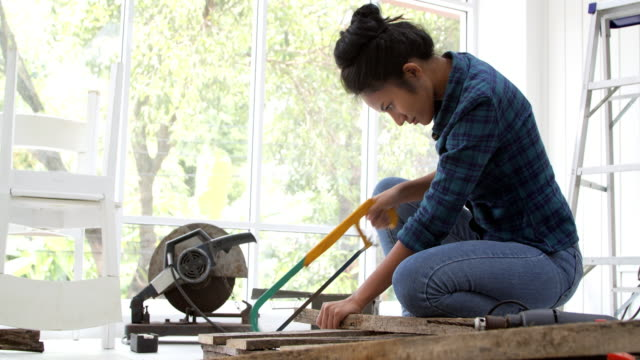 woman doing diy work, assembling furniture at home.women in stem - home improvement stock videos & royalty-free footage