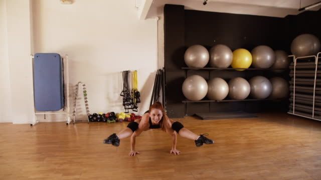Woman doing fitness and dance exercises in a parquet gym floor