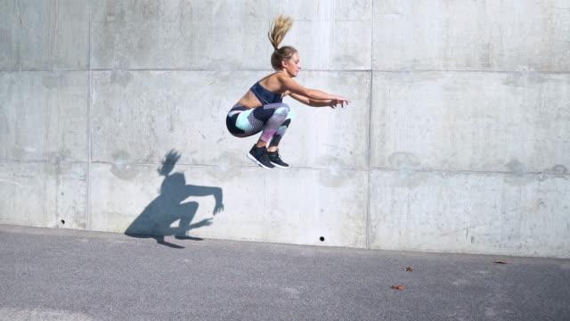 vídeos de stock, filmes e b-roll de mulher fazendo saltos de sapo - jogo de carniça