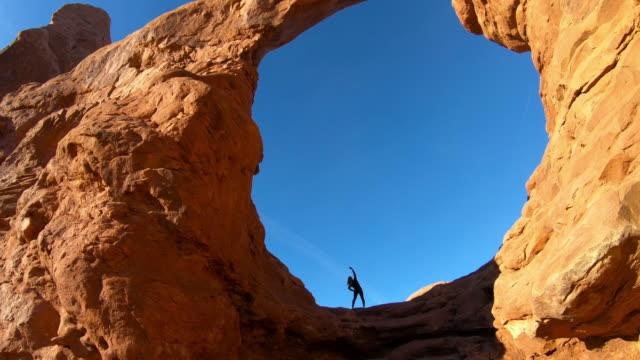 woman doing gymnastics exercise outdoors, Arches National Park
