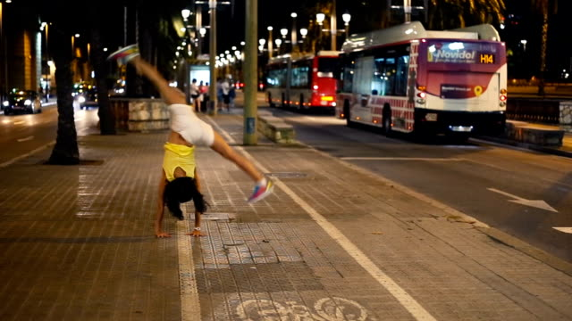 stockvideo's en b-roll-footage met woman doing half moon (head down feet up) in the city - acrobatiek