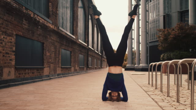 woman doing headstand in empty street - attitude stock videos & royalty-free footage