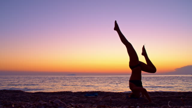 WS Woman doing headstand yoga exercises on the beach