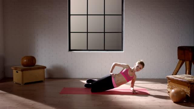frau machen ihr workout im fitnessraum (becken lift seitlich - knochen im beckenbereich stock-videos und b-roll-filmmaterial