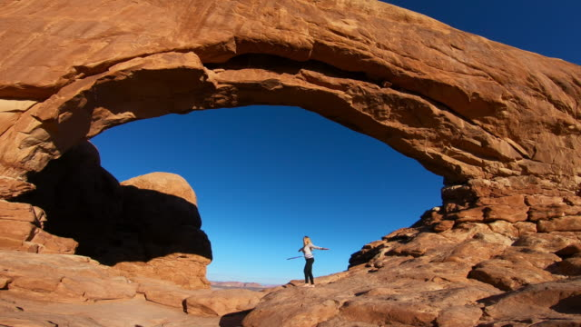 woman doing hula hoop, north window arch, Arches Park
