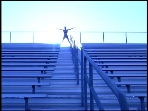 woman doing jumping jacks in stadium - hampelmannsprung stock-videos und b-roll-filmmaterial