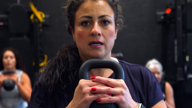 vídeos de stock, filmes e b-roll de cu woman doing kettlebell squats during fitness class in gym - estilo de vida ativo