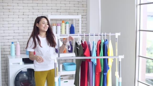 vidéos et rushes de femme faisant la lessive et séchant des vêtements à la maison - suspendre