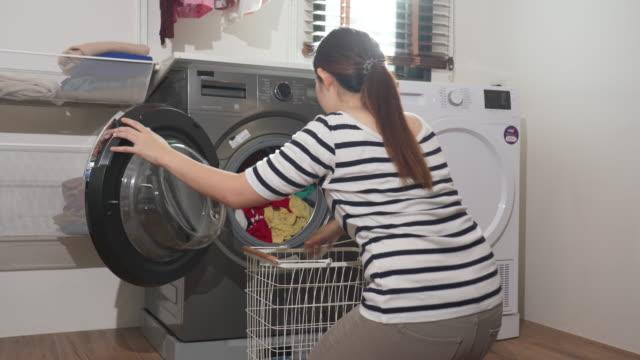 stockvideo's en b-roll-footage met vrouw die was doet en kleren in wasmachine laadt - wasmand
