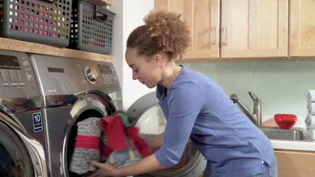 vídeos de stock e filmes b-roll de woman doing laundry at home - diário