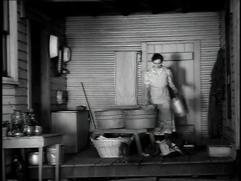1923 ws woman doing laundry by hand in washtubs while young girl prepares to clean oil lamps / united states - 1923 stock videos & royalty-free footage