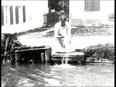 woman doing laundry on small pier in river / two young girls running up to woman / boy in lederhosen playing with girl wading in river woman washes... - 1910 stock-videos und b-roll-filmmaterial