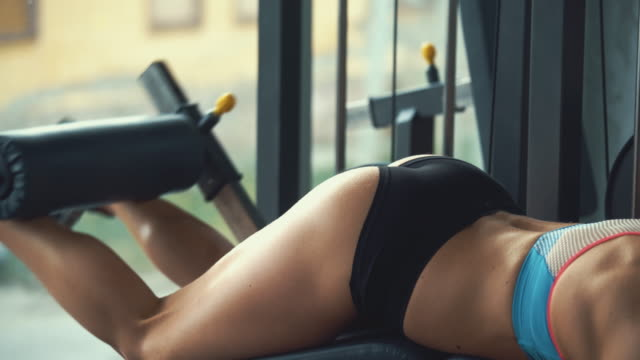 Woman doing leg curls at gym.