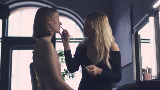 woman doing makeup for beautiful lady in studio - artista video stock e b–roll