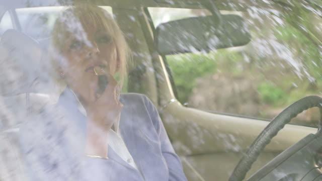woman doing make-up in car - solo una donna matura video stock e b–roll