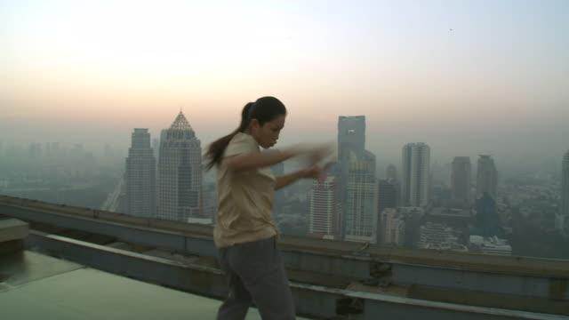 ms pov woman doing martial arts movements on rooftop / bangkok, bangkok, thailand - martial arts stock videos and b-roll footage