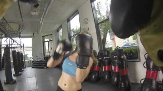 Woman doing Muay Thai/ kickboxing training at the gym. - Slow Motion