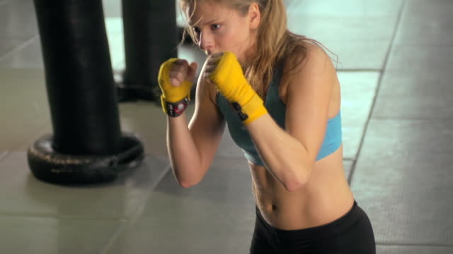 woman doing muay thai/kickboxing training at the gym. - slow motion - muay thai stock videos and b-roll footage