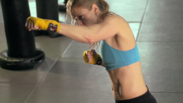 Woman doing Muay Thai/kickboxing training at the gym. - Slow Motion