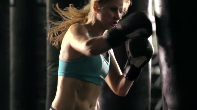 woman doing muay thai/kickboxing training at the gym. - slow motion - punch bag stock videos and b-roll footage