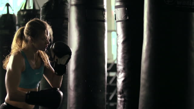 vídeos y material grabado en eventos de stock de woman doing muay thai/kickboxing training at the gym. - slow motion - boxeo mujeres