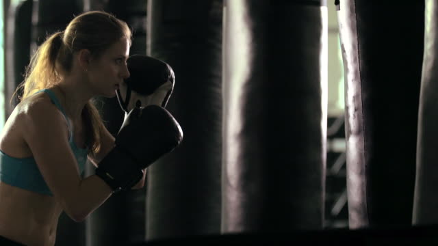 woman doing muay thai/kickboxing training at the gym. - slow motion - punch bag stock videos & royalty-free footage