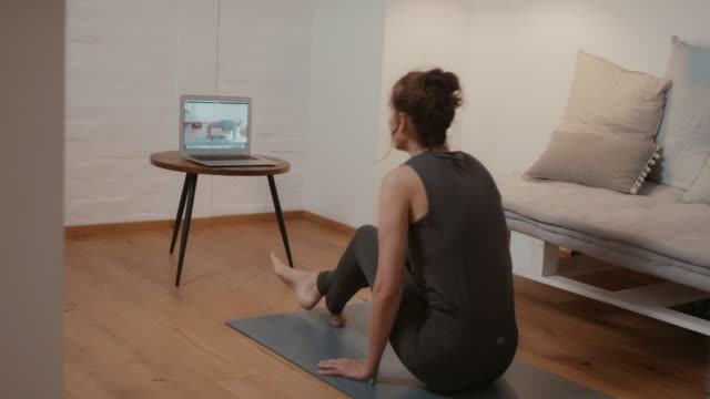 vídeos de stock, filmes e b-roll de woman doing online yoga class at home - tutorial
