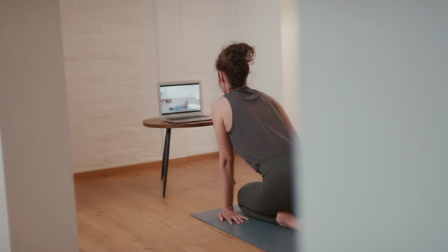 woman doing online yoga class at home - germany stock videos & royalty-free footage