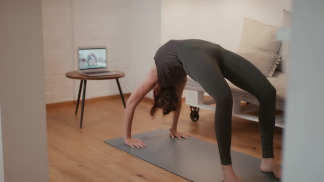 woman doing online yoga class at home - competition stock videos & royalty-free footage