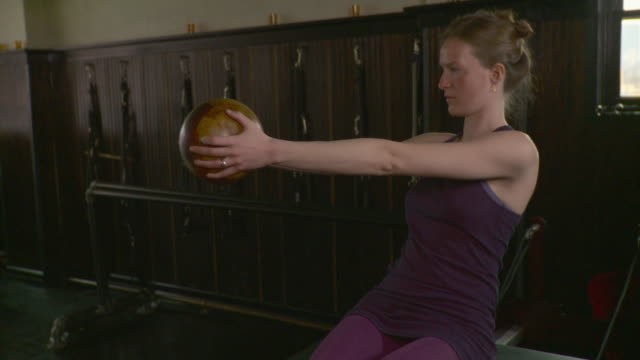 MS Woman doing pilates exercise with medicine ball with assistance from instructor / Brooklyn, New York, USA