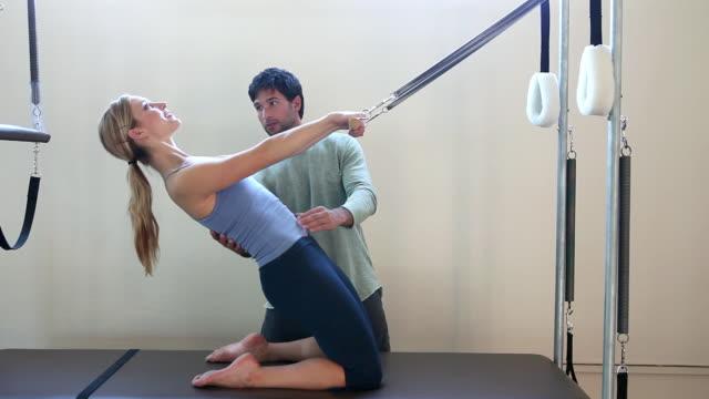 vídeos de stock, filmes e b-roll de woman doing pilates with fitness instructor - cabelo preso