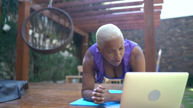 woman doing plank during a virtual exercise class at home - virtual event stock videos & royalty-free footage
