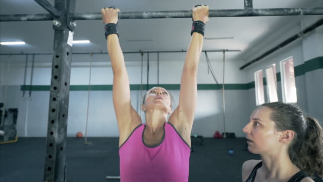 woman doing pull ups during a workout. - sbarra da ginnastica video stock e b–roll