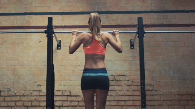 donna facendo pull-up in palestra - sbarra da ginnastica video stock e b–roll