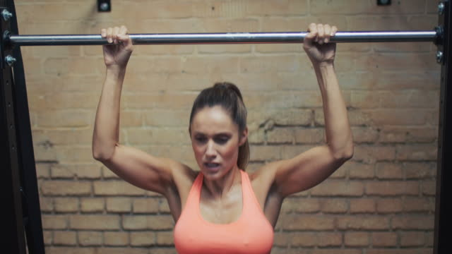 woman doing pull-ups in gym - chin ups stock videos and b-roll footage