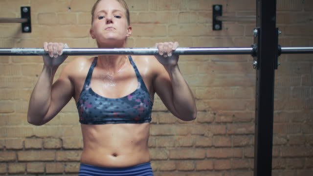 woman doing pull-ups in gym - horizontal bar stock videos and b-roll footage