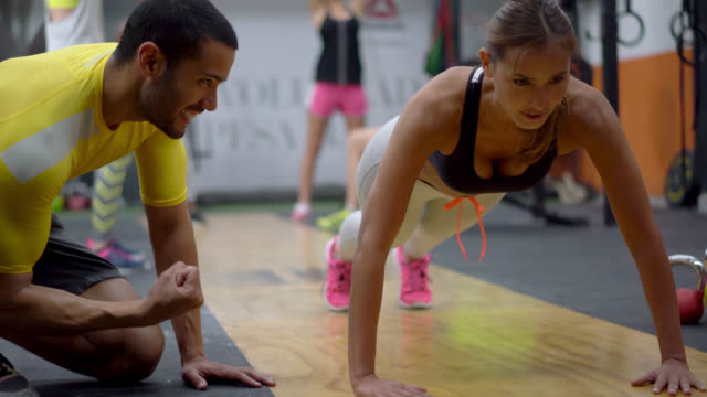 woman doing push ups and her personal trainer encouraging her - allenatore video stock e b–roll